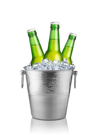 Botellas verdes de cerveza en el cubo de hielo aislado en el fondo blanco