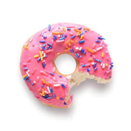 El rosado rosqueó el buñuelo con colorido asperja con la falta de la mordedura. Aislado en el fondo blanco e incluyen trazado de recorte Foto de archivo