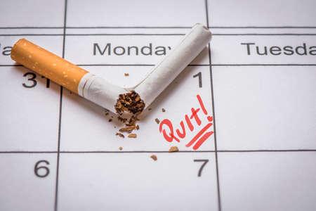Broken cigarette on calendar. Time to quit smoking concept Stock Photo