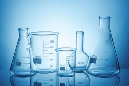 Laboratory glassware set with reflections on blue background Stock Photo