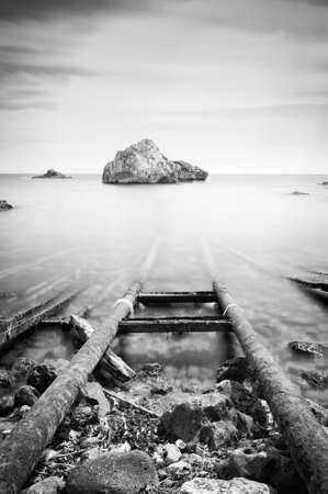 Black and white photo of sea and rocks, long exposure.