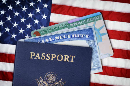 United States passport, social security card and resident card over american flag. Immigration concept Stockfoto