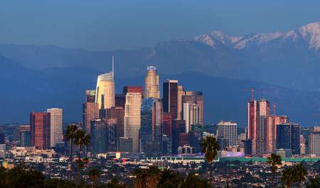 Skyline von Downtown Los Angeles mit schneebedeckten Bergen dahinter in der Dämmerung