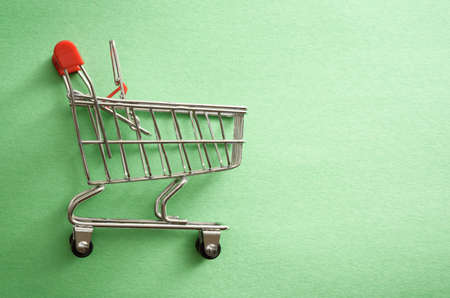 Empty shopping cart over green background. Flat lay, top view Stock fotó