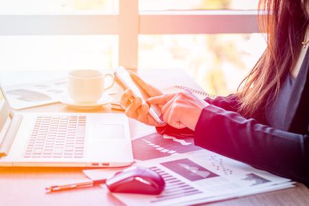 Sluit omhoog zakenlieden die bij een koffiewinkel met een document met een smartphone en een laptop computer werken. Stockfoto