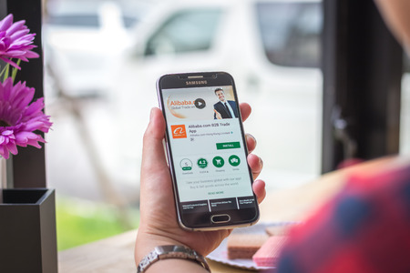Chiang Mai, Thailand - September 12, 2017: Samsung Galaxy S6 smartphone launches alibaba aliexpress application on the desk screen at the coffee shop.
