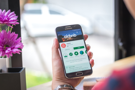 Chiang Mai, Thailand - September 12, 2017: Samsung Galaxy S6 smartphone launches airbnb application on the desk screen at the coffee shop.