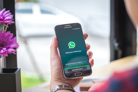 Chiang Mai, Thailand - September 12, 2017: Samsung Galaxy S6 smartphone launches whatsapp application on the desk screen at the coffee shop. Editorial