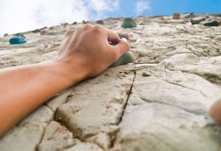 to climb: One hand to climb the cliff