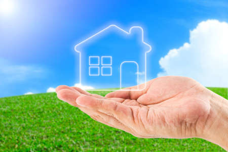 hands holding home  Green field under blue sky background photo