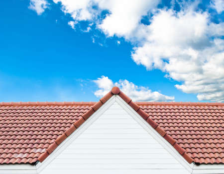 roofing: red rooftop against blue sky Stock Photo