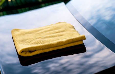 girl with towel: cleaning her new car using microfiber cloth