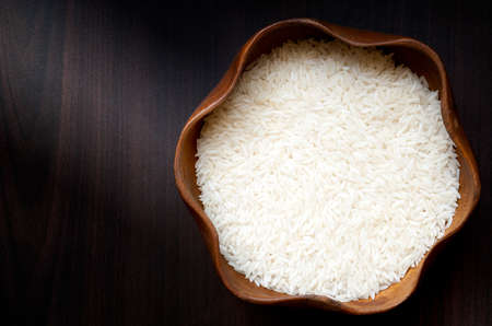Uncooked rice in wooden bowl photo