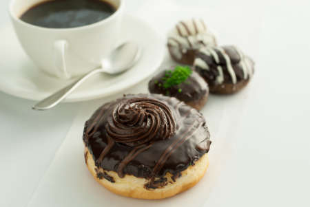 Chocolate donuts with coffee on table