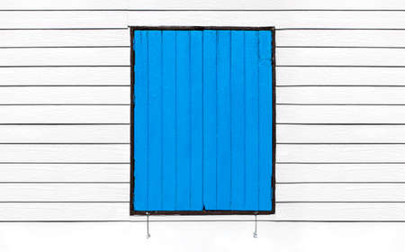 Blue wooden windows on white wooden wall   photo