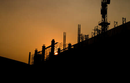construction site silhouetted at sunset
