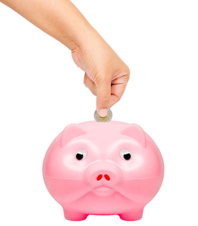 Putting coin into the piggy bank, isolated photo