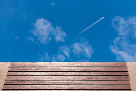 knothole: Wooden fenceand and airplane against blue sky background Stock Photo
