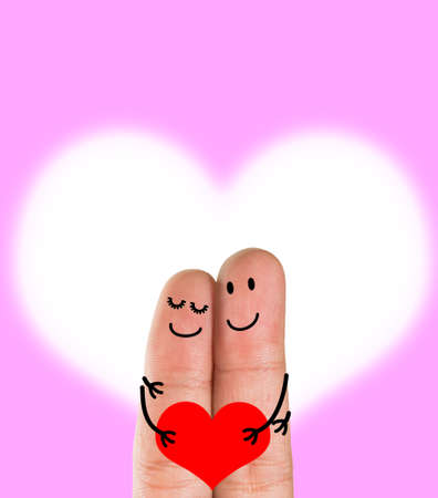 A happy finger couple in love  with painted smiley holding red heart, pink Heart background ,valentines day