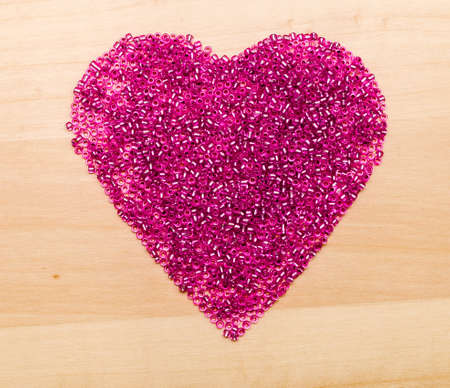 heart shaped: Plastic beads  in heart shaped on a wood background