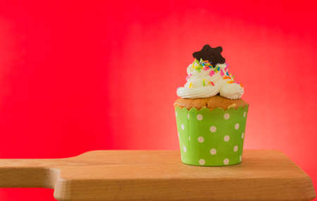 Cupcake against red background on wooden cutting board