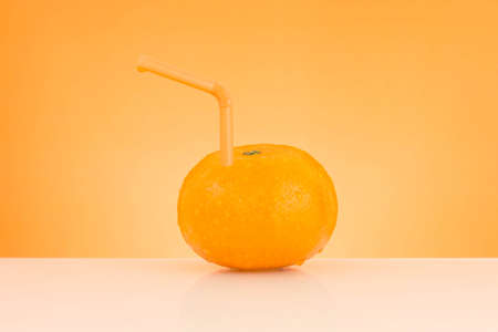 fresh orange juice on orange background and tube