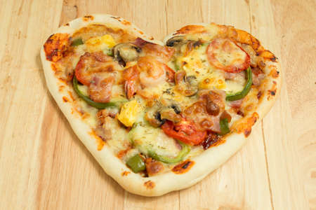 shaped: Heart shaped pizza on wood Stock Photo