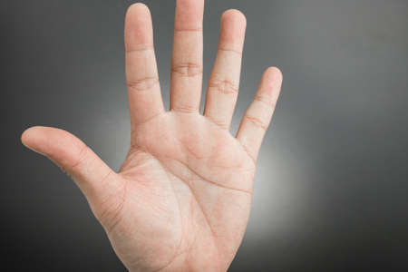 Man hand showing the five fingers isolated on a black background
