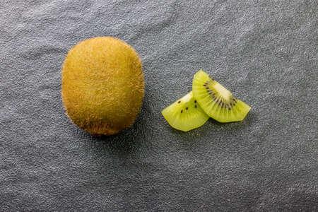 Kiwi fruit on top of black stone .top view
