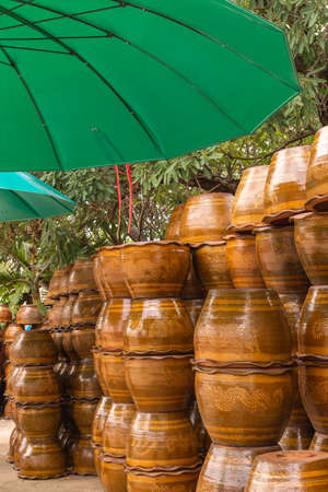 Stack of flowerpots made from clay , Thai style plant , Dragon pot style and Green umbrella Stock Photo