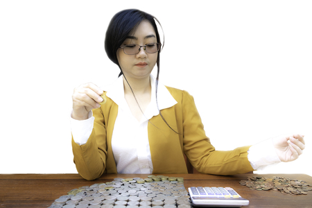 Business woman counting Stacked lots coins using Calculator on wooden desk, Portrait of beautiful happy young lady hands Pick up money top wood table with white background, Planning Investment and saving concept