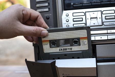 Women hand putting cassette into old fashioned audio tape player on top desk wood background