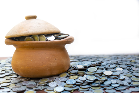 Coins in jar from on pile lots coin with white background, Money stack for business planning investment and saving concept