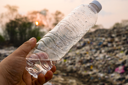 Plastic bottle in man hand on large garbage pile and pollution background
