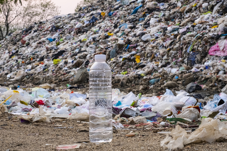 Plastic bottle on large garbage pile and pollution background