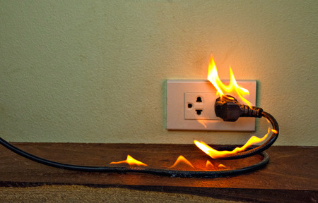 Spina del cavo elettrico in fiamme Divisorio della parete della presa, guasto di cortocircuito elettrico con conseguente bruciatura del cavo elettrico