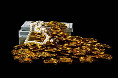 Stack bundles of 100 US dollars banknotes and gold coin on black background, Pearl jewelry necklace