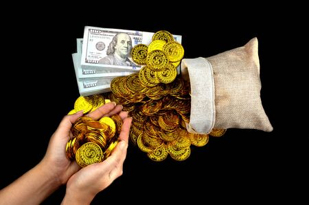 Hand holding gold coin in treasure sack and stack bundles of 100 US dollars banknotes on black background