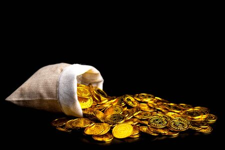 Stacking gold coin in treasure sack on black background, Money stack for business planning investment and saving future concept