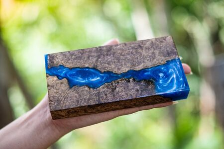 Hand holding casting epoxy resin Stabilizing persimmon burl wood abstract art background  写真素材
