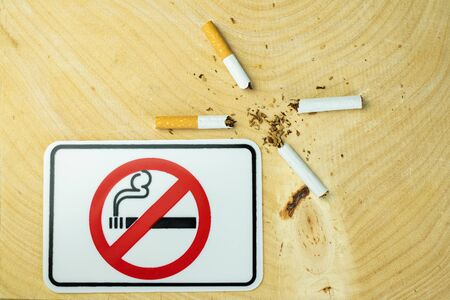 Close up of a cigarette and the sign no smoking showing on desk wood