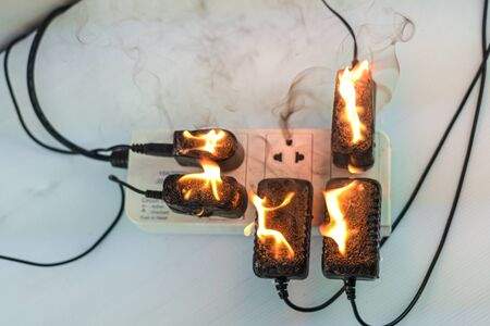 On fire adapter at plug Receptacle on white background, Electric short circuit failure resulting in electricity wire burnt Фото со стока