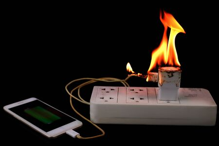 On fire Adapter smart phone charger at plug in power outlet at black background Stock Photo
