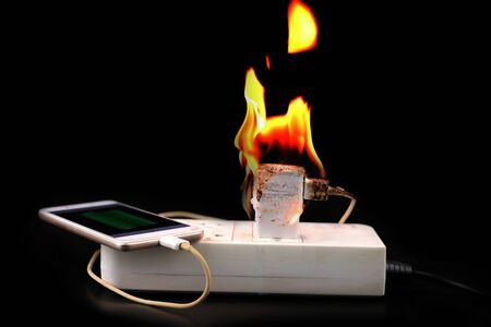 On fire Adapter smartphone-oplader bij stekker in stopcontact op zwarte achtergrond Stockfoto
