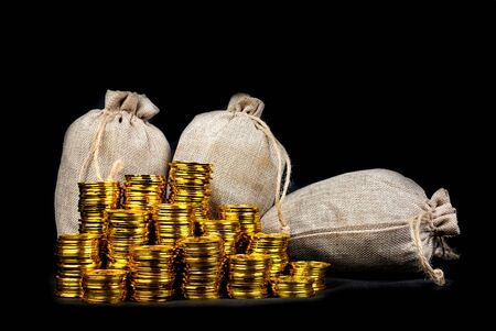 Stacking gold coin in treasure sack at black background