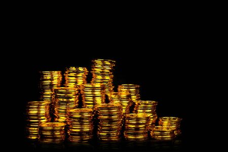 Stacking gold coin in treasure stack at black background