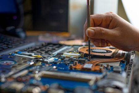 Technician repairing broken laptop notebook computer with screwdriver