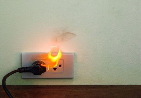 Spina del cavo elettrico in fiamme Divisorio della parete della presa, guasto di cortocircuito elettrico con conseguente bruciatura del cavo elettrico Archivio Fotografico