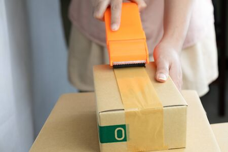 Women handle cutter adhesive tape sealing machine packing, parcel boxes stacked on each other at white background
