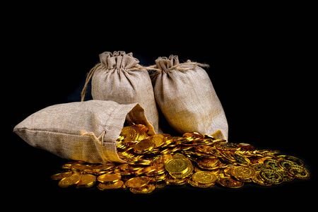 Lots of gold coin in treasure sack at black background
